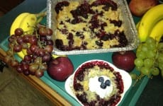 Blackberry Cobbler presented with fruit and a bowl dished up.
